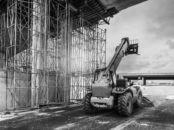 Construction forklift in action under bridge - black and white photo