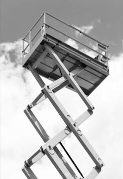 Scissor style personnel lift against cloudy sky