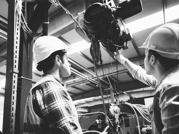 two men with hardhats at stationary crane indoors at industrial workspace