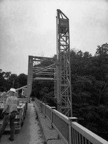 Bridge snooper crane extending down from bridge roadway to below